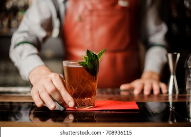 Barman holds a cocktail with mint in his hand. No face. Selective focus