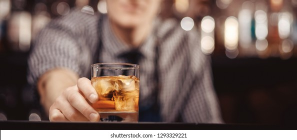 Barman holds out glass of whiskey with ice to male visitor. Concept rest in bar.