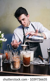 The barman in a leather tunic and white shirt is preparing a delicious cocktail for a women