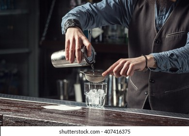 Barman makes cocktails with a shaker.