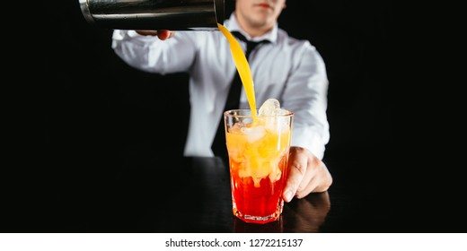 Barman making cocktail at nightclub.  Expert bartender preparing colorful cocktail at the bar. Professional barman mixing cocktail. Red and yellow alcoholic drink in glass on bar counter.