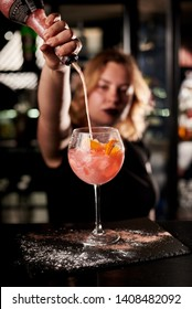Barman making cocktail with sparkling wine, Aperol and orange. Close up view focused on hands.