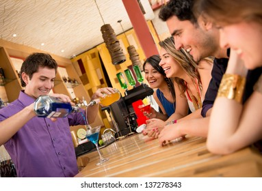 Barman making cocktails for a group of friends