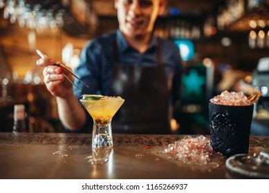 Barman making coctail with the help of forceps
