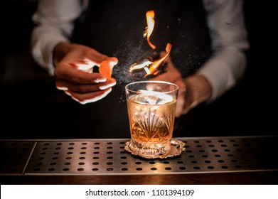 Barman making a fresh and tasty old fashioned cocktail with orange peel and smoke note on the bar counter