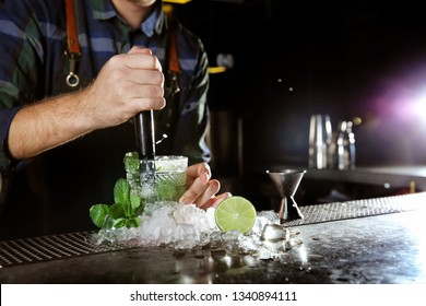 Barman making Mojito cocktail at counter in pub, closeup. Space for text
