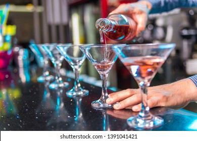 Barman making and serving alcohol cocktails in nightclub.
