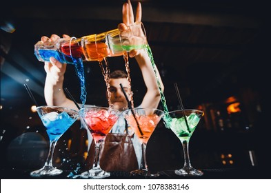 Barman mixes cocktail show with colorful alcoholic cocktails at bar counter.