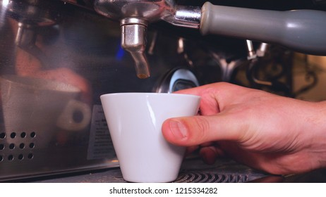 The barman on the coffee machine prepares fresh coffee and adds milk and sugar. Concept from: Barman, Coffee, Sugar, Coffee Machine, Man, Tattoo, Good morning.