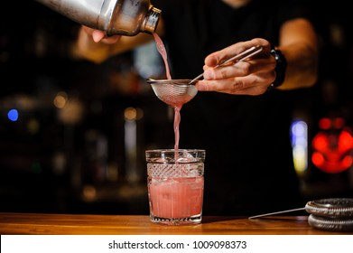 barman poured an alcoholic cocktail of pink color from the shaker through a strainer into a crystal glass using bar equipment