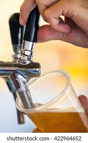 Barman pouring beer from a tap on keg.