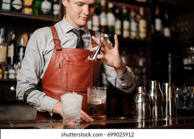 barman is pouring a cocktail in a glass