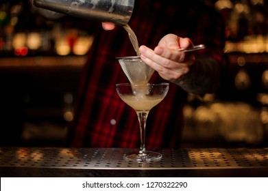 Barman pouring fresh and sweet juicy alcoholic cocktail from shaker into cocktail glass on the bar