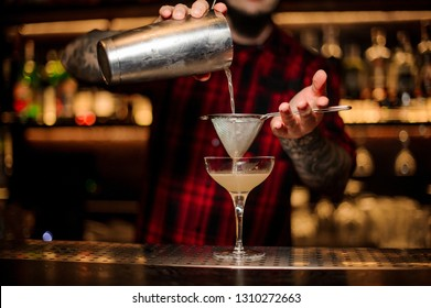 Barman pouring fresh and sweet juicy alcoholic cocktail from shaker into cocktail glass using strainer on the bar
