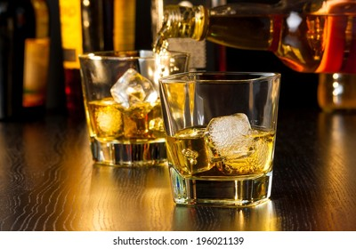 barman pouring whiskey behind whiskey glass on wood table