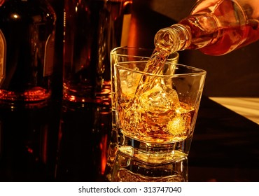 barman pouring whiskey in front of whisky glass and bottles on black table