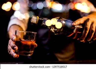 Barman pouring whiskey whiskey glass..