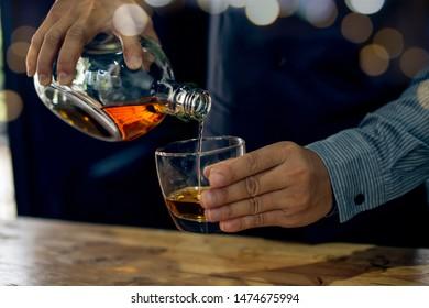 Barman pouring whiskey whiskey glass .