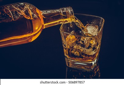 barman pouring whiskey whiskey with ice cubes in glass on black background, cool atmosphere, time of relax with whisky
