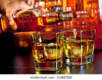 barman pouring whiskey on bar table lounge bar atmosphere
