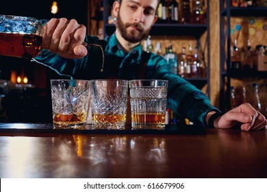 The barman pours alcohol into a glass. Close-up.