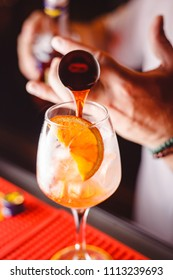 The barman pours Aperol into the cocktail of Aperol Spritz close up