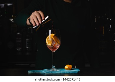 The barman pours Aperol into the cocktail of Aperol Spritz, dark background