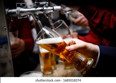 Barman pours beer into a glass