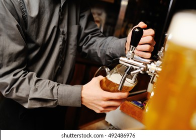barman pours beer into a glass on the background of the bar