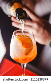 The barman pours champagne into the cocktail of Aperol Spritz close up