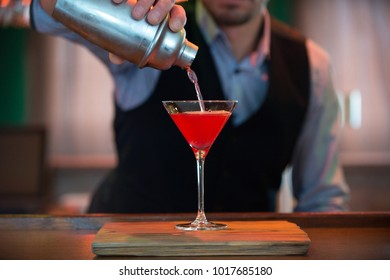 Barman pours a Cosmopolitan cocktail from a shaker into a glass