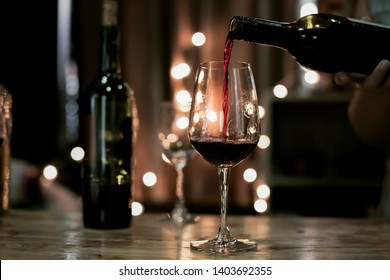 barman pours red wine in a glasses, on blackground bokeh