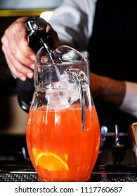 The barman pours soda water from a siphon into a jug with a soft fruit drink