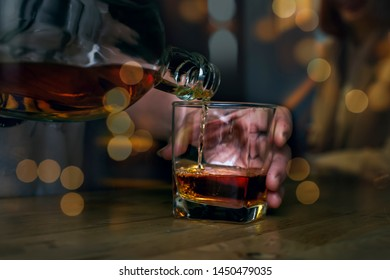 Barman pours whiskey in a glasses, on blackground bokeh