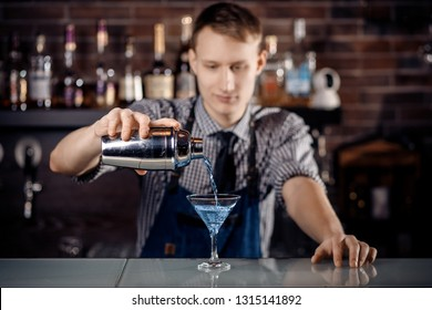 Barman prepares alcoholic cocktail in bar and with ice. Dark background.