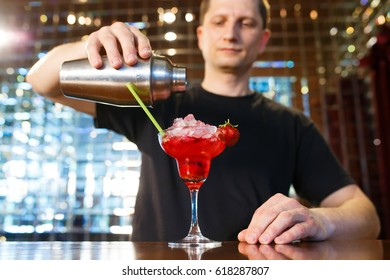The barman prepares alcoholic cocktail with strawberry.