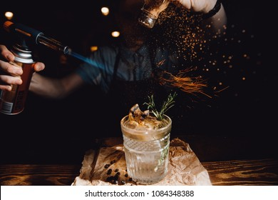 Barman prepares cocktail with orange and herbs in transparent glass on bar with alcohol. Uses burner with sparks. Dark background.
