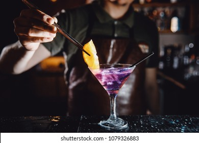 Barman prepares cocktail with orange and martini purple color on bar with alcohol. Uses tongs for decoration. Dark background.