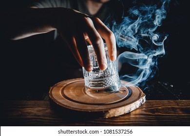 Barman prepares cocktail with smoke, raises glass, pours alcohol. Dark background.