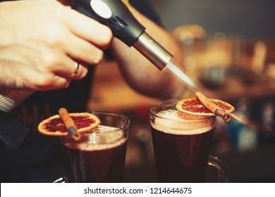 Barman prepares glintwein cocktail in cold autumn day. Bartender burns cinnamon sticks for mulled wine with gas torch in bar