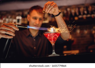 Barman prepares red cocktail ice herbs in transparent glass on bar with alcohol. Uses burner sparks.