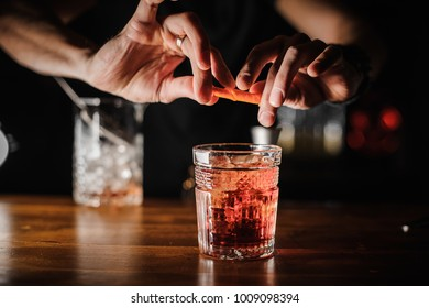 barman preparing alcoholic cocktail negroni of pink color in crystal glass with ice on the background of the bar counter