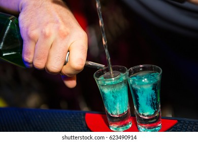 The barman is preparing a blue lagoon cocktail on the bar during a nightclub party