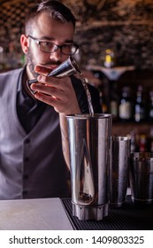 barman preparing cocktai and pours liquid into the jigger in a cocktail bar