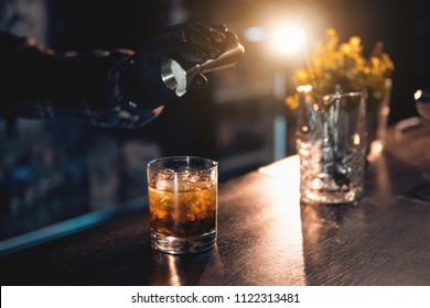 barman preparing luxury drink on the bar and with decoration; bartender making cocktail with icecream on backlighted background;