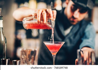 Barman, der roten Cocktail in der Martini-Klasse zubereitet und gießt. kosmopolitischer Cocktail auf Barhintergrund