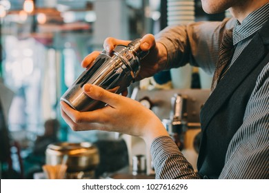 Barman In Pub Holding Shaker. Focus Is On Shaker.