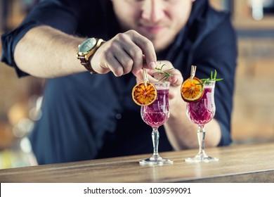 Barman in pub or restaurant  preparing a cocktail drink.