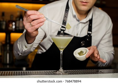 Barman putting a birch leaf decorating an alcoholic cocktail