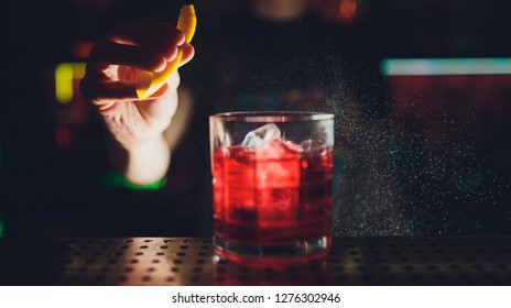 Barman s hands sprinkling the juice into the cocktail glass filled with alcoholic drink on the dark background.